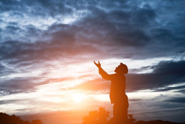 Silueta del hombre asiático apuesto orar.