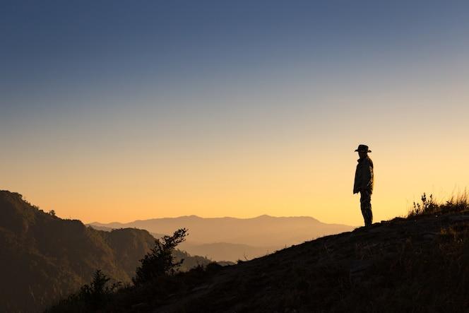 Silueta del hombre de pie en la cima de la montaña
