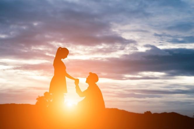 Silueta del hombre pida mujer para casarse en el fondo de la montaña.