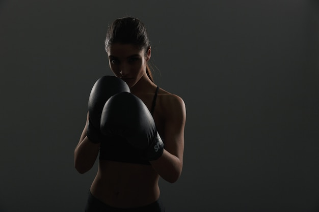 Silueta de deportista morena mirando y posando en guantes de boxeo, sobre pared oscura