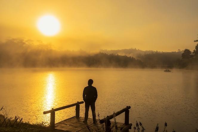 Silueta deprimido hombre de pie en el lago del río casa flotante