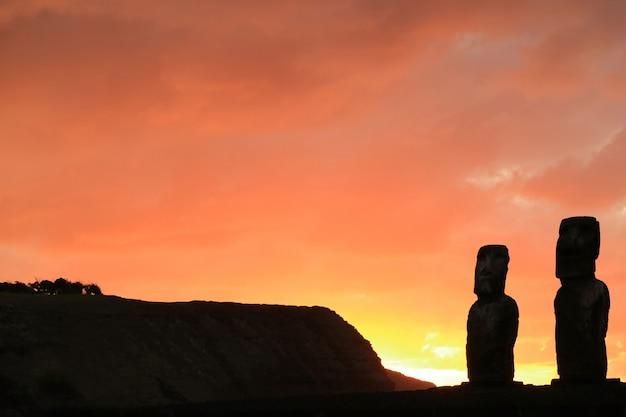 Silueta de dos de las 15 estatuas moai en ahu tongariki contra el cielo anaranjado de la salida del sol, isla de pascua, chile