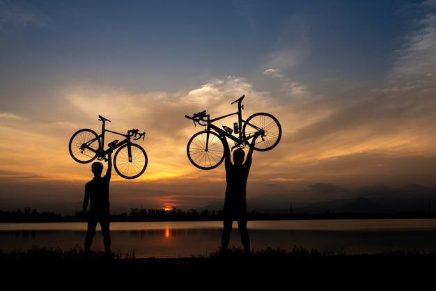 Silueta de dos ciclistas de bicicleta de carretera hombre sosteniendo bicicleta por encima de la cabeza por la mañana.