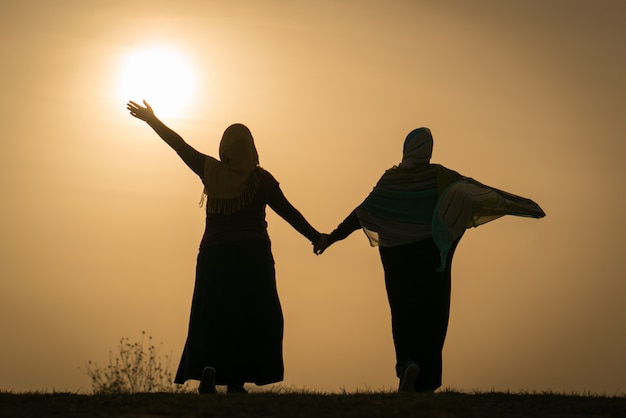 Silueta de dos hermanas musulmanas felices