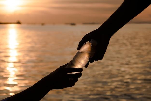 Silueta de dos manos ayudando / sosteniendo agua fresca en botella, enfoque selectivo y luz cálida, sosteniendo la mano