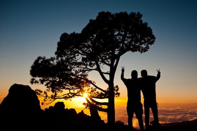 Silueta de dos mans muestra gesto de paz y admira la puesta de sol