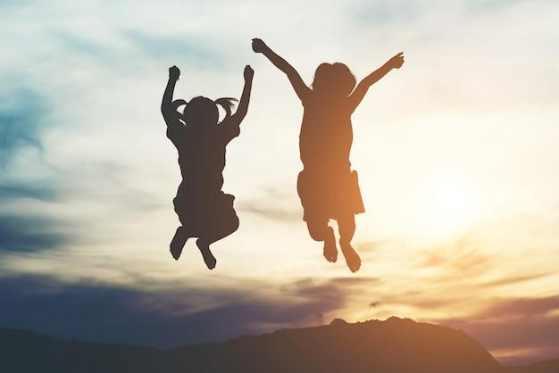 Silueta de dos niñas divirtiéndose en la naturaleza