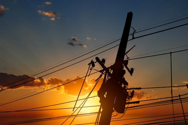 La silueta del electricista trabajador de alto voltaje está trabajando para solucionar los cortes de energía en la noche.