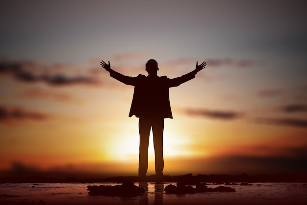Silueta del empresario levantó las manos y rezando a dios