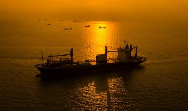 Silueta de envío de contenedores de carga en el mar y el fondo del amanecer