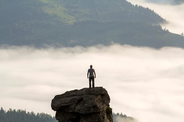 Silueta de escalador deportivo turístico en alta formación rocosa en valle de montaña llena