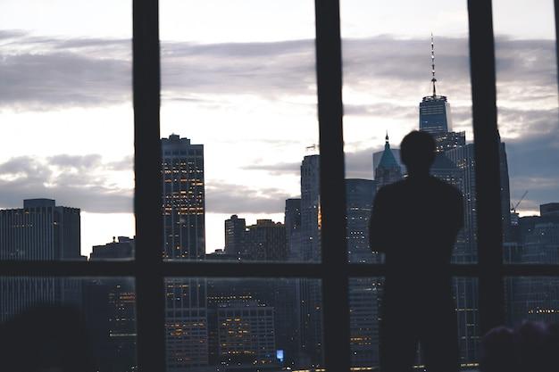 Silueta de un exitoso hombre de pie de una ventana con vistas a la isla de manhattan
