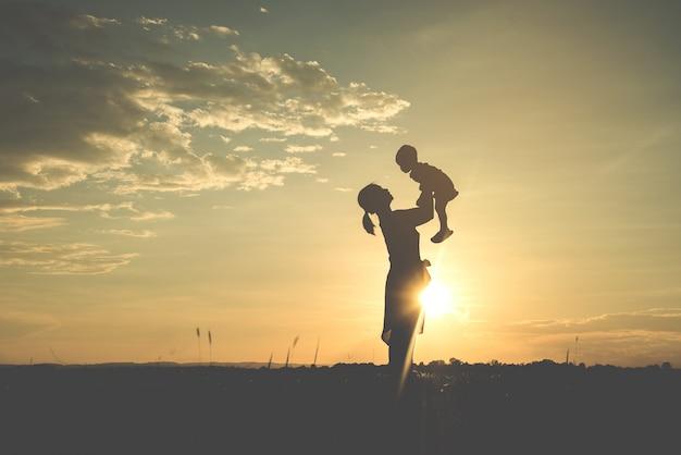 Una silueta de una familia armoniosa de la madre joven feliz al aire libre.
