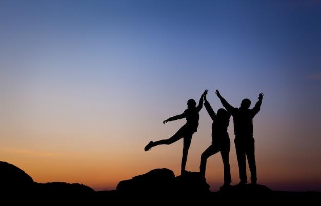 Silueta de la familia de la felicidad con los brazos levantados
