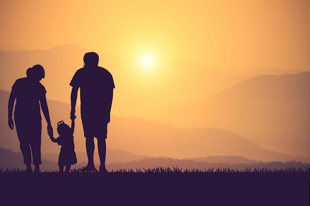 Silueta de una familia feliz y puesta de sol de tiempo feliz