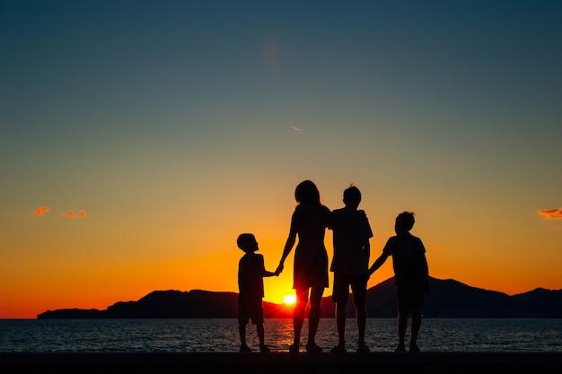Silueta de una familia con niños con el telón de fondo de la puesta de sol y el mar