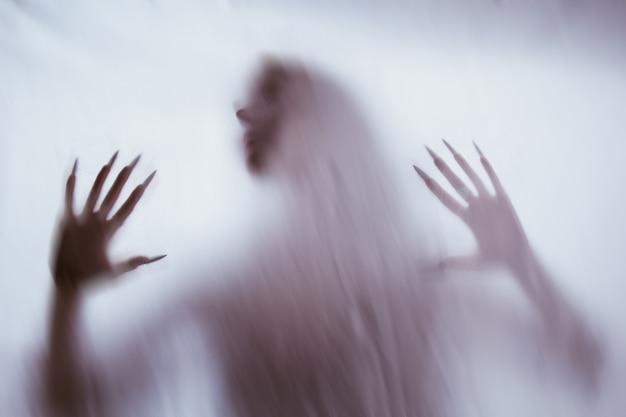 Silueta de una figura sexual femenina detrás de vidrio brumoso. concepto del espíritu de poltergeist del otro mundo. manos aterradoras de la muerte a través de la tela.