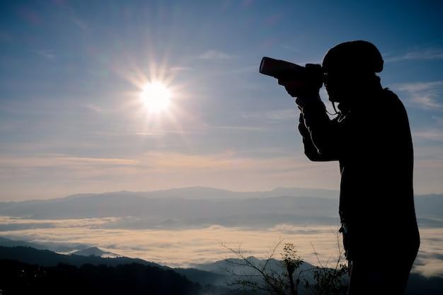 Silueta de fotógrafo libre y feliz con cámara al atardecer