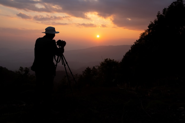 Silueta de un fotógrafo que dispara un atardecer en las montañas.