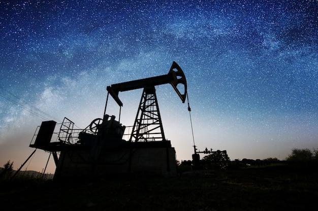Silueta del gato de la bomba de aceite que bombea en campo petrolífero en noche
