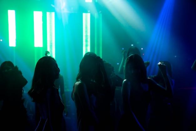 Silueta de gente baila en discoteca con música de dj en el escenario