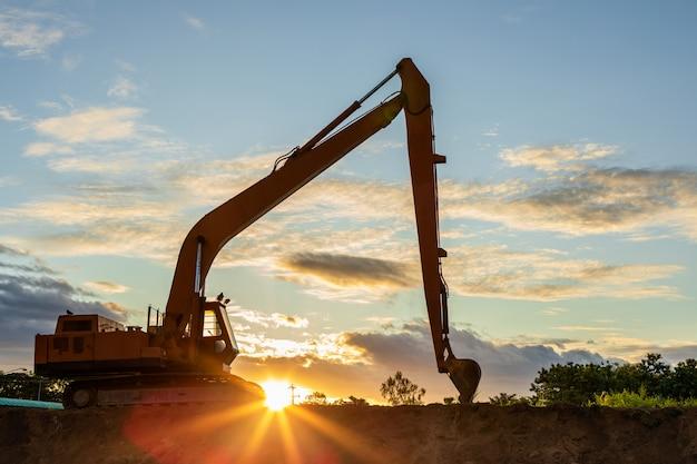 Silueta de una gran excavadora cavando el suelo en el sitio