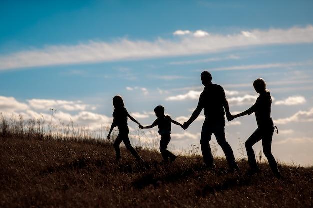 Silueta, grupo de familia feliz jugando en pradera, puesta de sol, verano