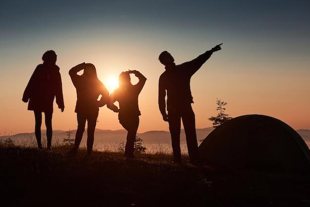 Una silueta de grupo de personas se divierte en la cima de la montaña cerca de la carpa durante la puesta de sol.