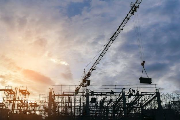 Silueta del grupo de trabajadores que trabajan en una obra de construcción.