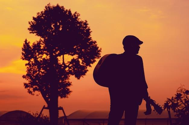 Silueta de guitarrista de pie, mirando el éxito, el concepto de silueta