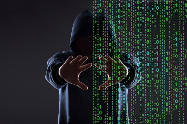 Silueta de un hacker en el capó sobre un fondo negro, concepto de realidad vs ciberespacio