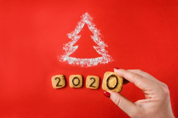 Silueta de harina de árbol de navidad con galletas dígitos 2020 sobre fondo rojo