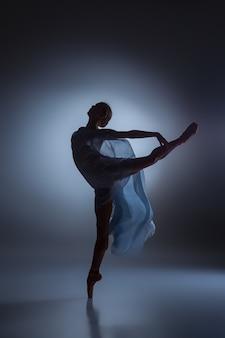 Silueta de hermosa bailarina bailando con velo sobre fondo azul oscuro