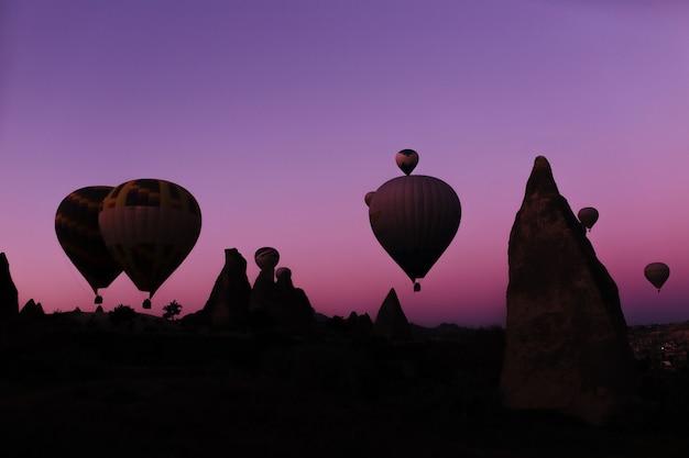 Silueta de hermosos globos aerostáticos al amanecer en capadocia