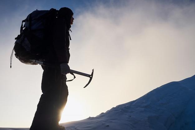 Silueta del hombre alpinista que va a la cima de la montaña al amanecer. sosteniendo una herramienta de hielo en sus manos