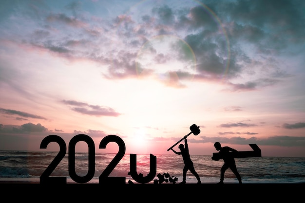 Silueta hombre aplastando el año 2020 y un hombre con el número uno para preparar el año 2021.