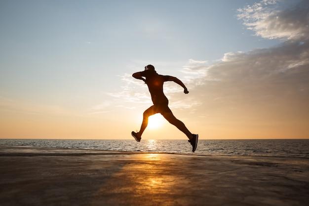 Silueta de hombre atlético de 30 años en pantalones cortos y camiseta entrenando y corriendo por el muelle junto al mar, y escuchando música a través de auriculares inalámbricos durante el amanecer