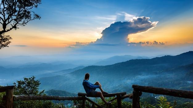 Silueta de un hombre con capa de montañas