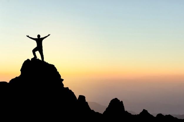 Silueta de un hombre en la cima de una montaña. deporte y concepto de vida activa