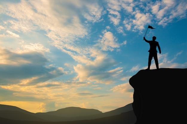 Silueta del hombre en la cima de la montaña sobre el cielo y la luz del sol, negocios, éxito, liderazgo, logros y personas
