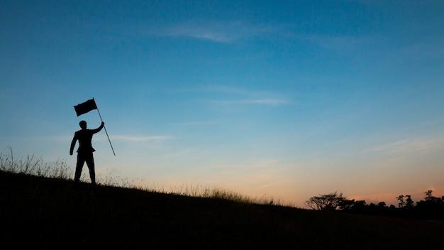 Silueta de hombre en la cima de la montaña sobre el cielo y la luz del sol