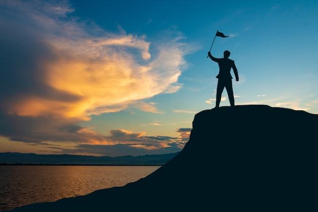 Silueta del hombre en la cima de la montaña sobre fondo claro de cielo y sol