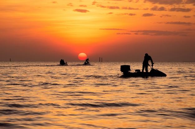 Silueta de hombre conduciendo una moto acuática en el mar durante la puesta de sol