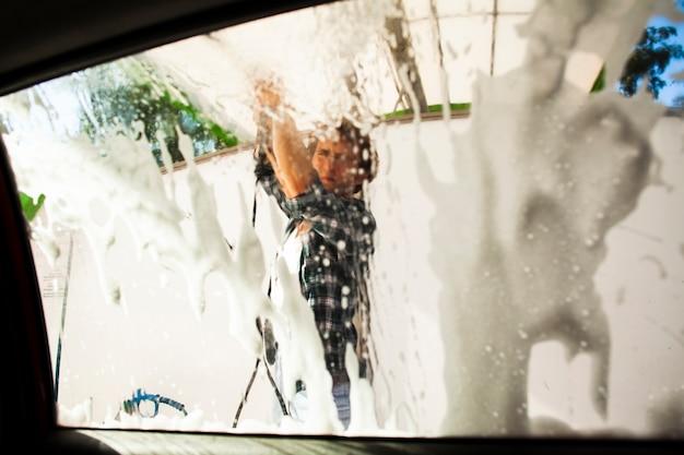 Silueta de hombre confuso lavando la ventana de un automóvil