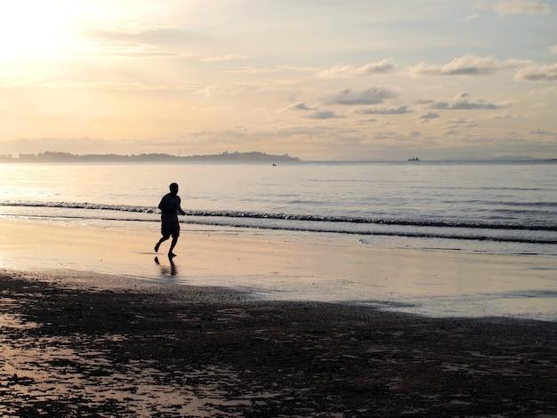Silueta de un hombre corriendo en la playa durante el atardecer