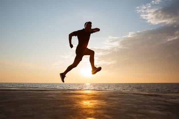 Silueta de hombre deportivo activo de 30 años saltando y corriendo por el muelle junto al mar y escuchando música a través de auriculares inalámbricos durante el amanecer