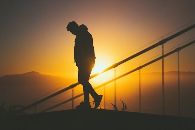 Silueta de un hombre joven caminando por la escalera detrás de los rieles de la escalera con hermosa vista del atardecer