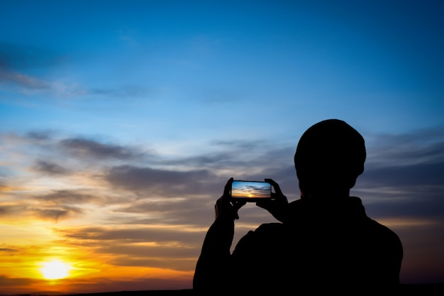 Silueta de hombre joven dispara puesta de sol en el teléfono, teléfono inteligente. viajar, caminar.