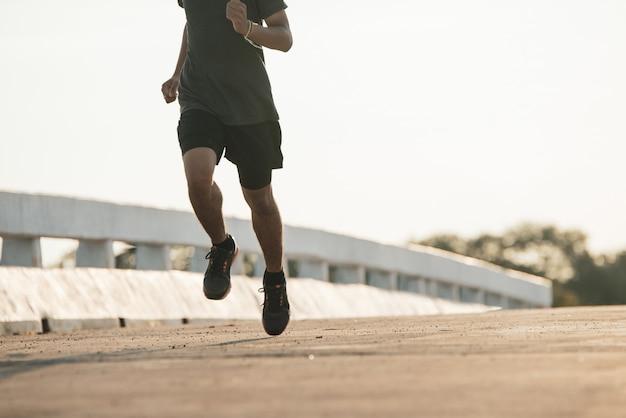 Silueta de un hombre joven fitness correr en sunrise