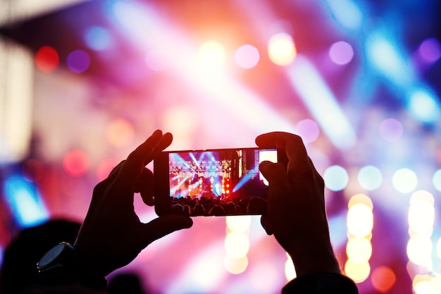 Silueta de hombre joven, tomando foto concierto de rock en el teléfono móvil, fiesta al aire libre